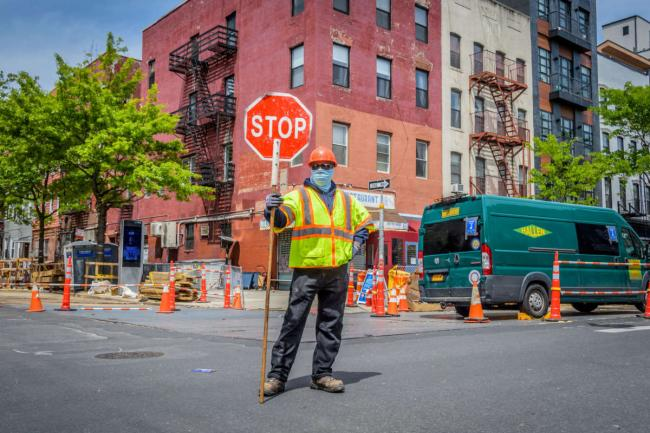 Construction workers wear protective face masks in the streets of Bushwick, New York, on May 19, 2020.