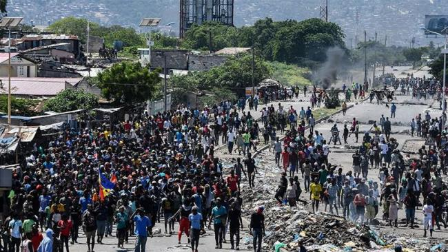 People march in Cite Soleil area of Port-au-Prince, Haiti during a protest to demand the resignation of President Jovenel Moise [Chandan Khanna/AFP]
