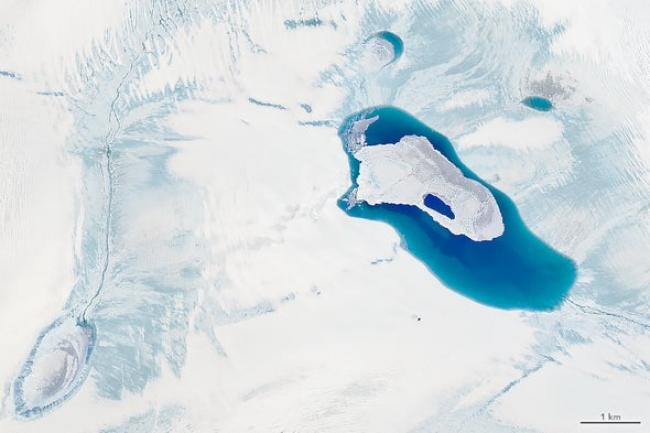 Meltwater ponds atop the ice in northwest Greenland on July 30 near the edge of the ice sheet. While summer melt along the periphery of the ice sheet is typical, melting that day covered a much higher area than usual because of a heat wave. Credit: NASA