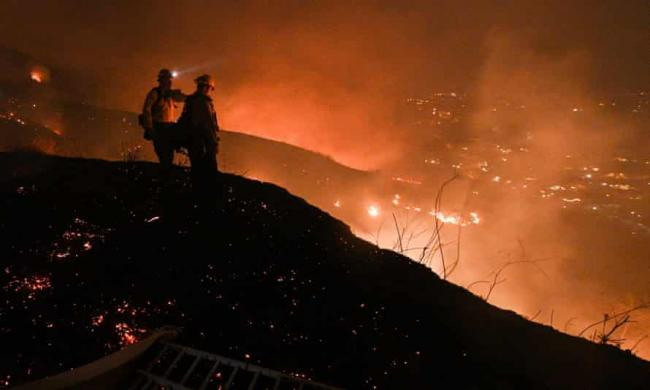 Firefighters look out over a burning hillside in Yorba Linda, California, on 27 October 2020. Photograph: Robyn Beck/AFP/Getty Images