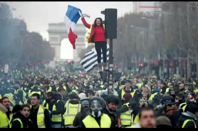 The Gilets Jaune, or Yellow Vests, fill the Champs Elysee./Photo by KRIS AUS67/Flickr