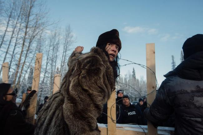 Sabina Dennis stands her ground as police dismantle the barricade to enforce the injunction filed by Coastal Gaslink pipeline at the Gidimt'en checkpoint near Houston, British Columbia, on 7 January. Photograph: Amber Bracken