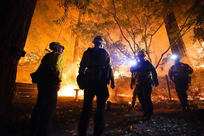 Firefighters make a stand in the backyard of a home in front of the advancing CZU August Lightning Complex fire on Friday 21 August in Boulder Creek, California. Photograph: Marcio José Sánchez/AP