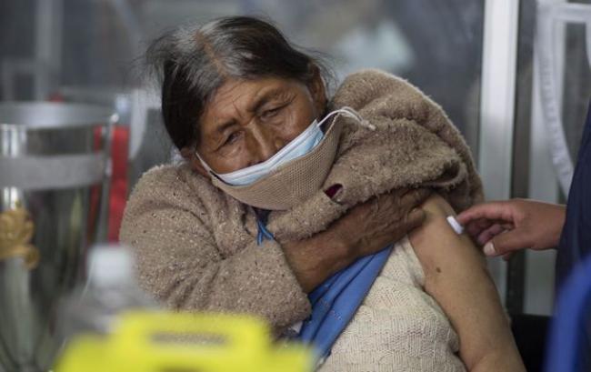 A woman gets a shot of the Sputnik V COVID-19 vaccine at the Universidad Publica de El Alto, during a vaccination drive for people over age 60 in El Alto, Bolivia, on May 6, 2021.  JUAN KARITA/THE ASSOCIATED PRESS