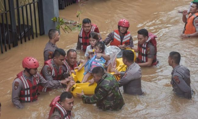 A rescue team evacuates a mother and child after flooding in Jakarta. Photograph: Agung Fatma Putra/SOPA Images/REX/Shutterstock