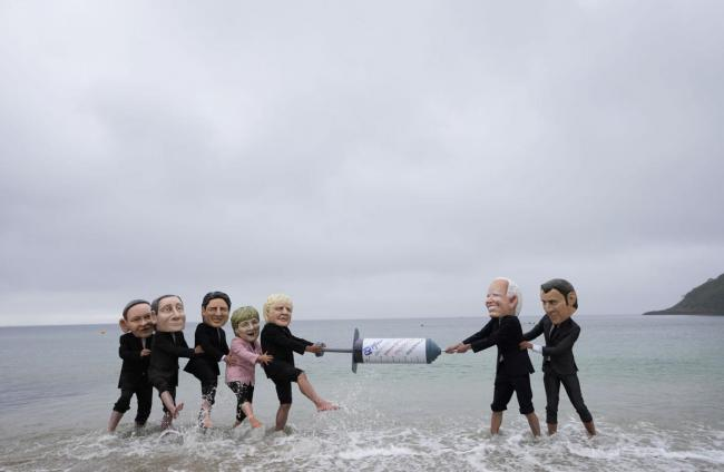 Activists wearing giant heads of the G7 leaders tussle over a giant COVID-19 vaccine syringe during an action of NGO's on Swanpool Beach in Falmouth, Cornwall, England, Friday, June 11, 2021. Leaders of the G7 begin their first of three days of meetings on Friday in Carbis Bay, in which they will discuss COVID-19, climate, foreign policy and the economy. Depicted from left to right, Japan's Prime Minister Yoshihide Suga, Italy's Prime Minister Mario Draghi, Canadian Prime Minister Justin Trudeau, German Cha