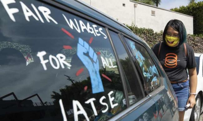 Crystal Kan, a storyboard artist, draws signs on union members' cars during a rally at the Motion Picture Editors Guild IATSE Local 700 on Sunday in Los Angeles. Photograph: Myung J Chun/Los Angeles Times/Rex/Shutterstock