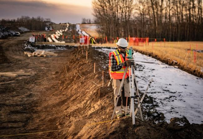 In this photo dated Dec. 5, 2019, a worker in Alberta takes measurements for the Trans Mountain pipeline expansion. Trans Mountain Photo / Facebook