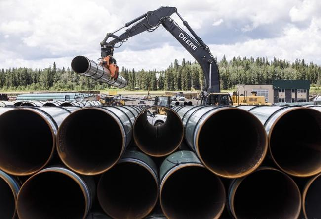 Pipe for the Trans Mountain pipeline is unloaded in Edson, Alta. on Tuesday, June 18, 2019. File photo by The Canadian Press/Jason Franson