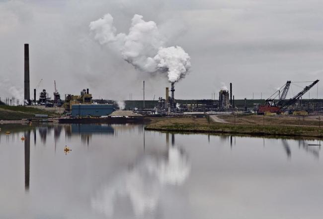 An oil sands extraction facility is reflected in a tailings pond near the city of Fort McMurray, Alberta on June 1, 2014. File photo by The Canadian Press/Jason Franson