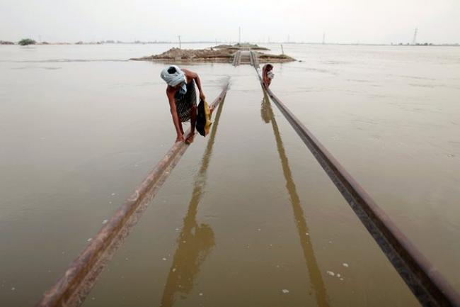 Villagers use part of a damaged railway track to cross floodwaters in Sultan Kot, Sindh province after torrential monsoon rains triggered Pakistan's worst natural disaster on record in 2010. Photograph: Damir Sagolj/Reuters