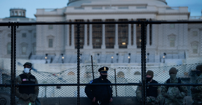 A Capitol Police officer stands with members of the National Guard behind a crowd-control fence surrounding Capitol Hill a day after a pro-Trump mob broke into the U.S. Capitol on January 7, 2021, in Washington, D.C. (Photo: Brendan Smialowski/AFP via Getty Images)