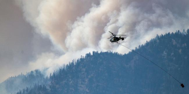 A helicopter prepares to make a water drop as smoke billows along the Fraser River Valley near Lytton, British Columbia, Canada, on July 2, 2021. Photo: James MacDonald/Bloomberg via Getty Images