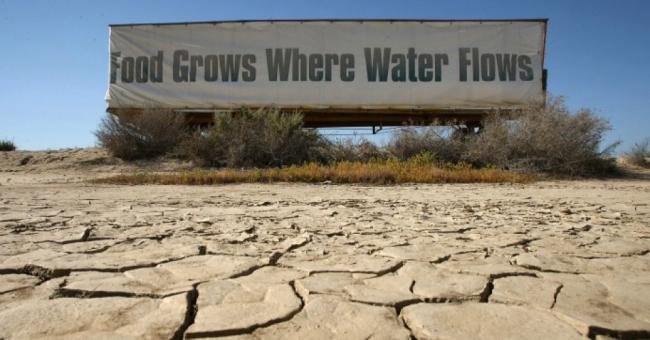 """A sign on a farm trailer reading """"Food grows where water flows"""" hangs over dry, cracked mud at the edge of a farm April 16, 2009 near Buttonwillow, California. (Photo: David McNew/Getty Images)"""