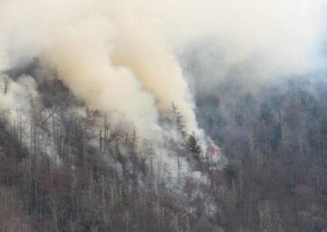 Smoke rises from wildfires in the Great Smoky Mountains near Gatlinburg, Tenn., on Tuesday. Great Smoky Mountains National Park
