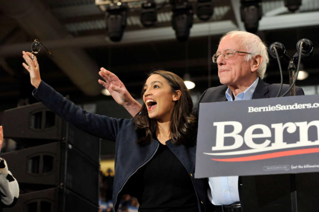 Rep. Alexandria Ocasio-Cortez and Sen. Bernie Sanders wave to his supporters at a rally at the University of New Hampshire in Durham, New Hampshire, on February 10, 2020.SAUL LOEB / AFP VIA GETTY IMAGES