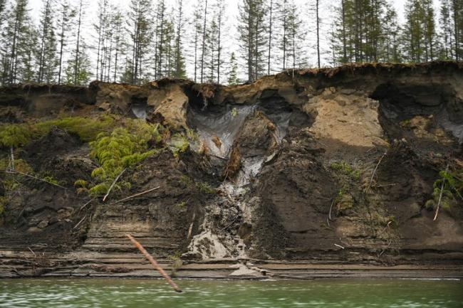 Permafrost, seen at the top of the cliff, melts into the Kolyma River outside of Zyryanka, Russia, in July 2019. A new study has found that methane is being released not only from thawing wetlands but also from thawing limestone. (Michael Robinson Chavez/The Washington Post)