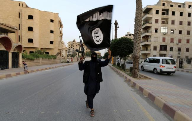 A member loyal to the Islamic State in Iraq and the Levant (ISIL) waves an ISIL flag in Raqqa in June 2014. (Reuters/Stringer)