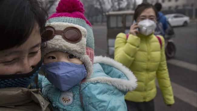 Pedestrians wear masks against the smog outside a hospital in Beijing. A new study outlines the myriad ways climate change is already worsening human health and causing premature deaths. (Kevin Frayer / Getty Images)