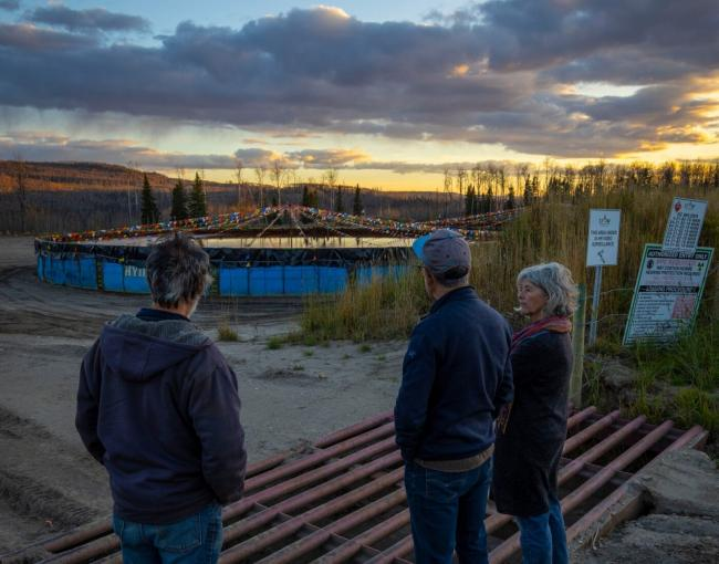 Hans Kirschbaum (left), reporter Ben Parfitt and Anja Hutgens look at a pool filled with fracking wastewater at the top of the hill above the ranchers' property. The couple is worried encroaching natural gas operations will contaminate their water source. Photo: Matt Miles / The Narwhal