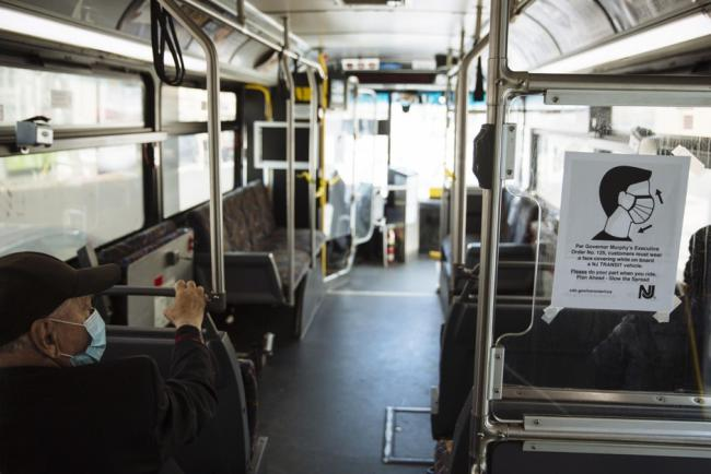 A sign advising passengers to wear face masks is displayed on a New Jersey Transit bus in Atlantic City. Angus Mordant/Bloomberg
