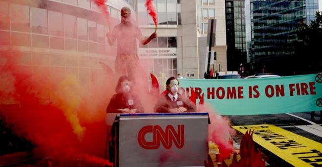 Rebels from Extinction Rebellion DC (XRDC) set off smoke flares and dumped ash outside CNN's DC offices on Friday, September 18, in protest at news outlet's coverage of the wildfire crisis. Credit: Gabe Cowan (XRDC)