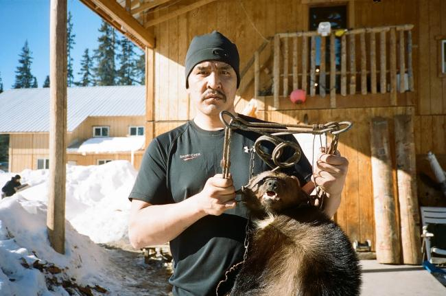 Johnny Morris, Gidimt'en Clan, poses with a wolverine in front of the Unist'ot'en Healing Centre. Trapping and other land based cultural activities are part of Healing Centre programming. Photo by Michael Toledano