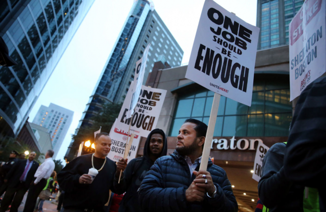 Workers and supporters picket outside the Sheraton Boston by Marriott in Boston on October 3, 2018. Building the world anew under a new social order is the hardheaded realism the working class must face. CRAIG F. WALKER / THE BOSTON GLOBE VIA GETTY IMAGES