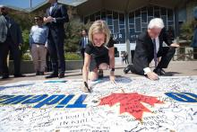 Alberta Premier Rachel Notley and Kinder Morgan Canada president Ian Anderson sign a message of support for pipeline expansion at an event in Calgary on May 30, 2018. Twitter photo posted by Rachel Notley