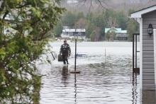 A man walks between flooded houses in Constance Bay northwest of Ottawa on April 26, 2019. Photo by Kamara Morozuk