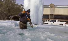 Kaleb Love, a municipal worker, breaks ice on a frozen fountain in Richardson, Texas, on Tuesday, as freezing temperatures grip the state. Photograph: LM Otero/AP