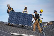 Workers wearing Iron & Earth clothing set up solar panels. Photo courtesy of Iron & Earth / Facebook