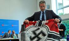 """A German police officers shows a Nazi flag confiscated from the far-right group Besseres Hannover. Contrarian climate scientist and conservative media favorite Roy Spencer posted a rant on his blog against those he calls """"global warming Nazis."""" Photograph: Alexander Koerner/AP"""