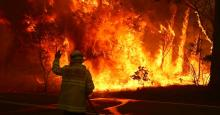 Fire and Rescue personnel run to move their truck as a bushfire burns next to a major road and homes on the outskirts of the town of Bilpin on December 19, 2019 in Sydney, Australia. (Photo: David Gray/Getty Images)