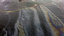 Fuel slicks spread around the tug Nathan E. Stewart, stranded on a reef it struck. (Marilyn Slett)