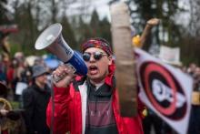 Cedar George-Parker addresses the crowd as protesters opposed to the Kinder Morgan Trans Mountain pipeline extension defy a court order and block an entrance to the company's property, in Burnaby, B.C., on Saturday April 7, 2018. THE CANADIAN PRESS/Darryl Dyck