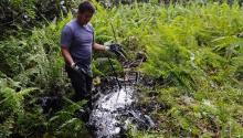 A member of an Indigenous community in Ecuador shows the contamination by Chevron in the Amazon. | Photo: AFP