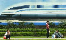 A vision of high-speed growth … a billboard features a magnetic levitation train in Shanghai. Photograph: Liu Jin/AFP