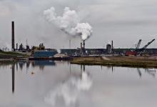 The Syncrude oil sands extraction facility is reflected in a tailings pond near the city of Fort McMurray, Alta., on June 1, 2014. File photo by The Canadian Press/Jason Franson