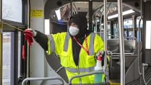 A city worker is cleaning a bus at the end of the line. Photo: Jim West / jimwestphoto.com.