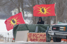 A protester stands between Mohawk Warrior Society flags at a rail blockade on the 10th day of demonstration in Tyendinaga, near Belleville, Ont., Sunday, Feb. 16, 2020. LARS HAGBERG/THE CANADIAN PRESS