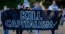 "Participants hold a ""Kill Capitalism"" banner while marching through Central Park in New York City. (Photo: Erik McGregor/LightRocket via Getty Images)"