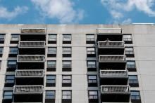 A man stands on the balcony of a high-rise building in New York City. (Bryan Thomas / Getty Images)