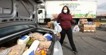A volunteer with Forgotten Harvest loads food into a vehicle at a mobile pantry April 14, 2020 in Detroit, Michigan. The organization distributes food throughout the metro area, which has seen an uptick in demand due to the COVID-19 pandemic. (Photo: Gregory Shamus/Getty Images)
