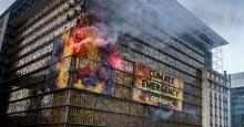 Greenpeace activists on Thursday wrap the E.U. summit venue in Brussels with images of giant flames, setting off clouds of smoke, flares and sounding a fire alarm to urge European government leaders to take immediate action to respond to the climate emergency. (Photo: Eric De Mildt/Greenpeace)