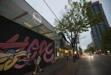 A woman wearing a protective face mask walks past the boarded up shops along Robson Street in downtown Vancouver on May 4, 2020.  JONATHAN HAYWARD/THE CANADIAN PRESS