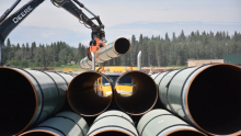 A truck loaded with pipe is unloaded at the Trans Mountain yard in Edson, Alta. (Terry Reith/CBC)