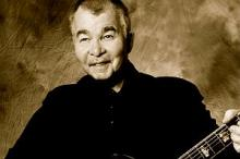 John Prine performing with guitar in later years.