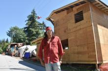 Johnny Lee stands in front of a carver's cabin he is building at Camp Cloud. Photograph By KELVIN GAWLEY