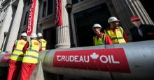 Greenpeace activists unfurl banners after building a wood and card 'oil pipeline' outside the Canadian High Commission, Canada House, to protest against the Trudeau government's plans to build an oil pipeline in British Columbia on April 18, 2018 in London. (Photo: Chris J Ratcliffe/Getty Images)